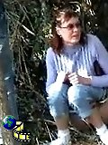 Lady pees under a tree and gets spied-on